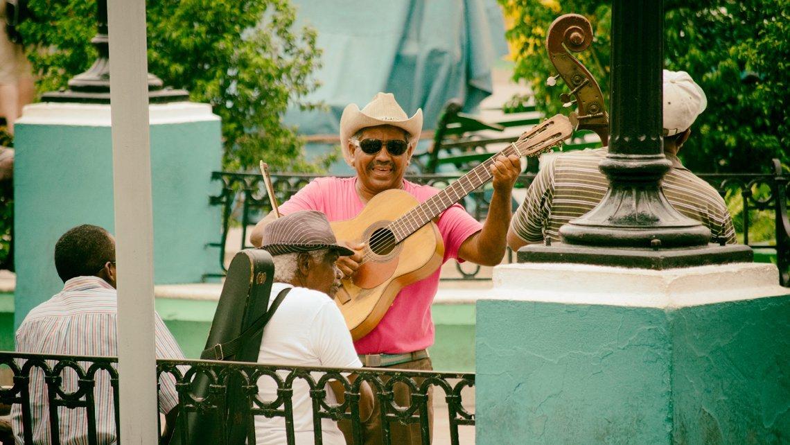 Musicos cantan a turistas en el Parque Cespedes de la ciudad de Santiago de Cuba